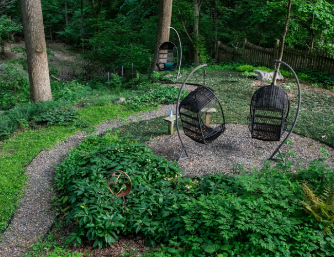 Two wicker swing chairs provide a relaxing way to view the native plant surroundings at Barbara Schubert's home. Photo by Ben Israel.