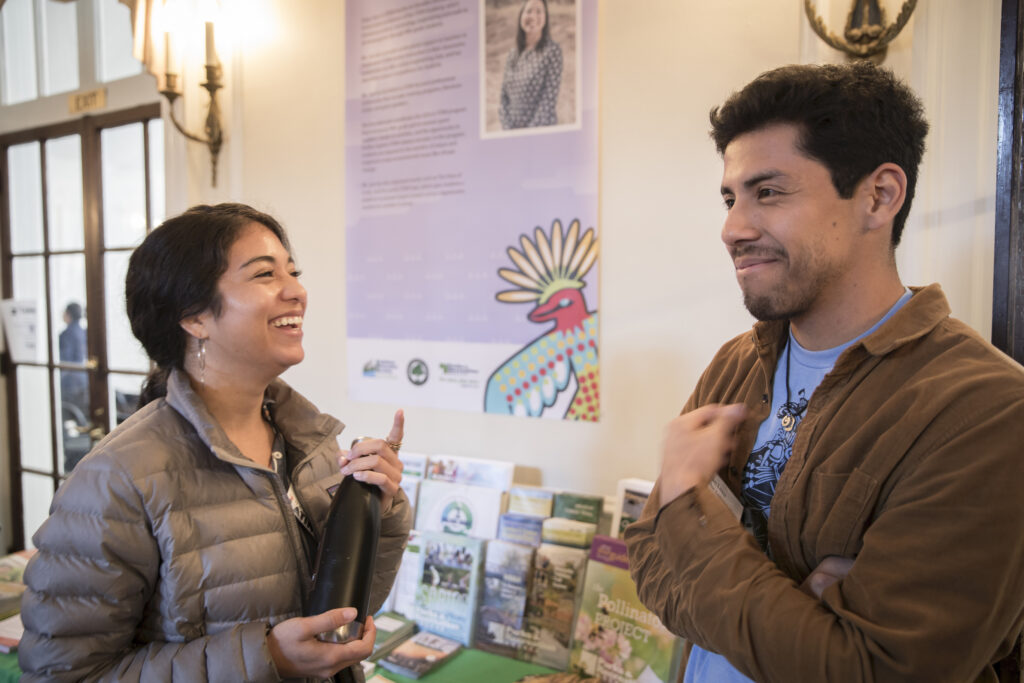 A Latina woman and Latino man talk in front of a beautiful banner with a colorful bird illustration at Naturally Latinos Conference 2019